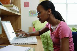 Young woman sitting at desk using laptop, in student dormitory